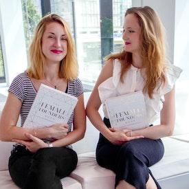 本を手に持っていてソファに座っている2人の女性