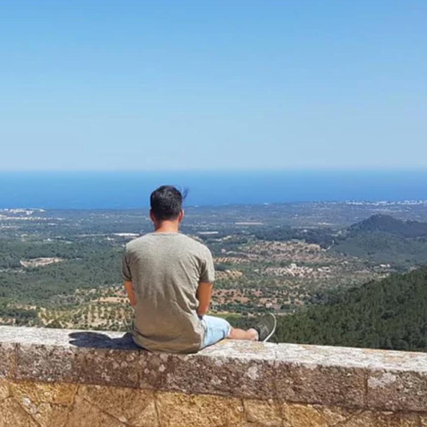 Eine Person sitzt auf einem Felsvorsprung und blickt auf das Meer